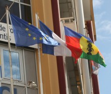 The French and Kanak flags fly together with the European union flag