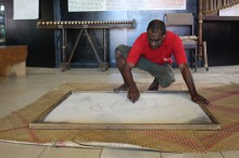 Tour Guide Edgar Hinge draws traditional sand pictures using a grid and continuous line. Picture by: Jane Mahoney