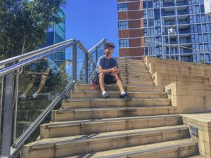 Young man sits at the top of a high set of stairs staring thoughtfully down at the camera.